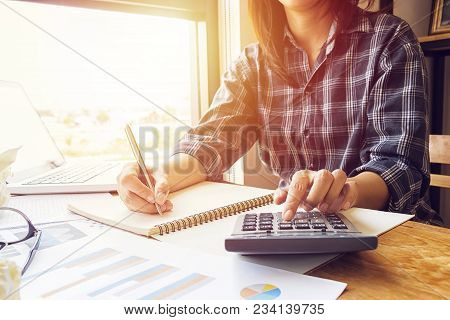 poster of Asian Business Woman Using Calculator For Accounting And Analyzing Investment In Front Of Computer L