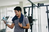 Muscular Asian Young Handsome Man Wipes Sweat With Towel And Drinking Water While Resting After Work poster