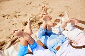 Soles of bare feet of girls lying on sandy beach on hot summer day and enjoying rest poster