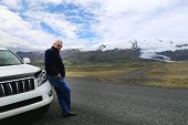 Senior Mature Confident Man Standing Near Suv Car. Scenic Mountain Landscape On The Background. Trav poster