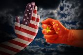 Trade Conflict, Usa Flag On A Stop Hand And China Flag On A Fist Against A Dramatic Cloudy Sky poster