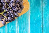 Grapes On A Blue Wooden Table. Branch Of Fresh Ripe Red Grapes. Beautiful Background With A Branch O poster
