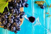 Grapes And Wine Glass On A Blue Wooden Table, Top View. Branch Of Fresh Ripe Red Grapes. Beautiful B poster