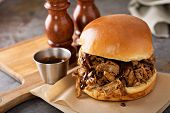 Pulled Pork Sandwich With Bbq Sauce On The Table poster