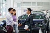 Young Asian Salesman Greeting Couple In Car Dealership poster