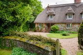 A typical traditional English country thatched house or cottage in rural Southern England UK poster