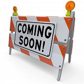 An orange and white construction barricade sign with the words Coming Soon to announce and introduce