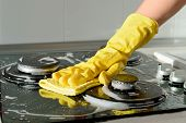In A Yellow Rubber Glove, A Hand Cleans A Gas Stove. Kitchen Cleaning poster