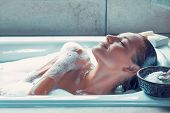Portrait of a woman with closed eyes of pleasure taking bath at home, female with pleasure enjoys ba poster