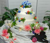 image of three tier  - Wedding cake with three tiers and flowers on a table at a wedding reception - JPG