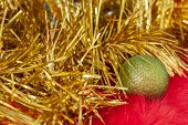 Green Christmas Ball On Red Fur And Christmas Golden Tinsel. Tinsel Is Like A Christmas Tree Branch. poster
