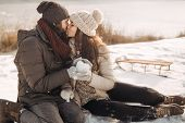 Happy Couple In Love Sitting On Snow Having Fun In Warm Casual Winter Clothes On A Sunny Day In Wint poster