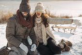 Happy Winter Couple Smiling Having Fun, Fooling Around Like Children In Winter Park Near Snowy River poster