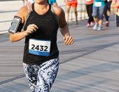 A Female Runner Is Running A 10k Race On A Boardwalk With A Phone Strapped On Her Arm And The Runner poster