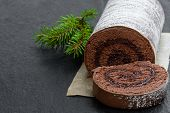 Chocolate  Yule Log Christmas Cake Coated With Milk Chocolate On Black Stone Background poster