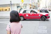 Young Woman Walking In Hongkong Street With Taxi Cab In Background. Traveler Asian Girl In Hongkong  poster