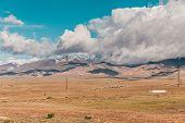 Panorama Of Desert Landscape On Background Snow-capped Mountain Peaks. View Mountain In With Peaks I poster