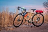 touring bicycle at dusk with headlight on in late fall or winter scenery in northern Colorado - a gr poster