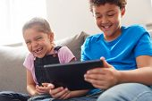 Brother And Sister Sitting In Lounge At Home Watching Movie On Digital Tablet Together poster