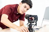Young asian male blogger setting up camera for recording live vlog video tutorial session at home. I poster