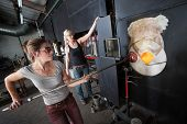 foto of blast-furnace  - Two female glass artists working at a blast furnace - JPG