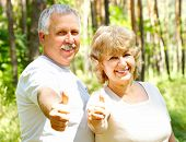 stock photo of elderly couple  - Smiling happy elderly couple in the summer forest - JPG