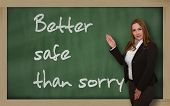 image of saying sorry  - Successful beautiful and confident woman showing Better safe than sorry on blackboard - JPG