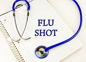 picture of flu shot  - Flu shot text over a white notebook wrapped in a blue stethoscope - JPG