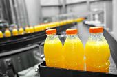 stock photo of sugar industry  - Orange juice bottles on factory assembly line