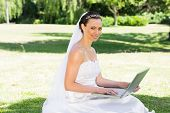 Portrait of smiling bride using laptop in garden