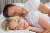 Relaxed young couple lying in bed with eyes closed at home