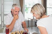 Serious mature couple with drinks while playing chess at home