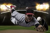 image of ball cap  - Baseball Player on a red uniform on a baseball Stadium - JPG