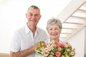 Senior couple smiling at camera holding bouquet of flowers at home in living room