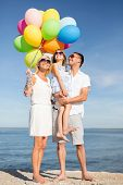 summer holidays, celebration, children and people concept - happy family with colorful balloons at s