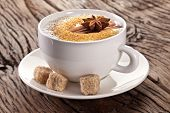 Cup of cappuccino decorated with spices and cubes of brown sugar near it.