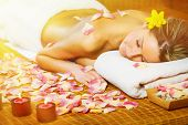 Beautiful woman having relaxing in spa massage salon.