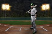 foto of ball cap  - Baseball Player on a Green Uniform on baseball Stadium.