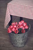 Vintage rustic photo of bouquet of spring tulips in a wicker basket on wooden floor