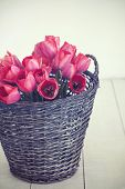 Vintage rustic photo of bouquet of spring tulips in a wicker basket on white wooden floor