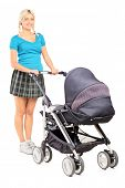 Full length portrait of a young woman pushing a baby stroller isolated on white background