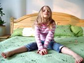 Young girl sitting on a bed
