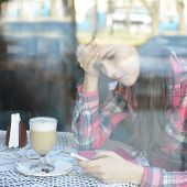 Young woman drinking coffee and use her smartphone sitting indoor in urban cafe. Cafe city lifestyle