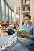 Happy student sitting in school library with classmates in background
