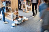 Student sitting on floor in library classmates walking blur motion