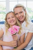 Happy mother and daughter with rose bouquet in house