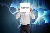 Businessman holding card saying solution against global business graphic in blue
