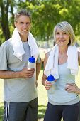 Portrait of happy couple after a workout with towels and water bottles in park