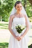Portrait of beautiful bride holding bouquet while standing in park