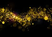 Gold glittering background .Glittering stars on bokeh background. Sparkling glitters on black backgr